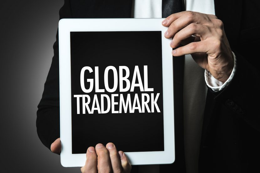 man in business suit holding ipad on international trademark law